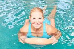 Sênior de sorriso na aptidão do aqua com um auxílio nadador imagem de stock royalty free