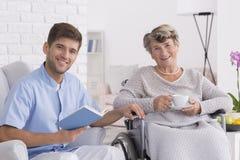 Sênior de sorriso na cadeira de rodas com assistente imagens de stock royalty free