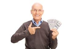 Sênior deleitado que guarda uma pilha de dinheiro fotografia de stock royalty free