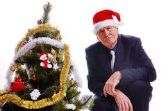 Sênior do homem de negócios que senta-se perto da árvore de Natal Imagens de Stock Royalty Free