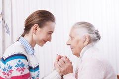 Sênior e cuidador que guardam as mãos em casa fotos de stock