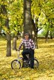 Sênior e sua bicicleta no parque do outono Foto de Stock Royalty Free