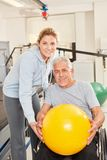 Sênior e terapeuta com bola do exercício foto de stock royalty free