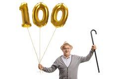 Sênior feliz com um balão dourado do número cem foto de stock