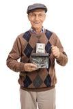 Sênior feliz que destrói uma nota de dólar em uma retalhadora de papel Imagens de Stock