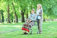 Sênior na cadeira de rodas que senta-se no parque com sua esposa Fotografia de Stock
