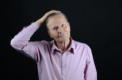 Sênior que afaga sua cabeça Imagem de Stock