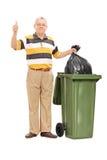 Sênior que dá um polegar acima por um balde do lixo Fotografia de Stock Royalty Free
