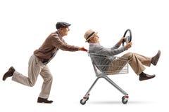 Sênior que empurra um carrinho de compras com um outro sênior com um steeri fotografia de stock
