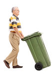 Sênior que empurra um grande balde do lixo verde Fotografia de Stock