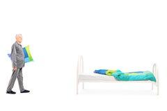 Sênior que guarda um descanso e que vai para a cama Fotografia de Stock