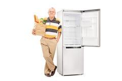 Sênior que guarda um saco de mantimento por um refrigerador vazio Fotografia de Stock