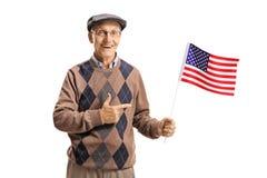 Sênior que guarda uma bandeira americana e apontar Imagem de Stock Royalty Free