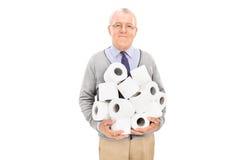 Sênior que leva uma pilha do papel higiênico Fotos de Stock Royalty Free