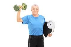 Sênior que levanta um peso dos brócolis Fotos de Stock Royalty Free