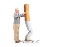Sênior que põe para fora um cigarro gigante Imagens de Stock Royalty Free