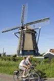 Sêniores do ciclismo e moinho de vento histórico Fotografia de Stock