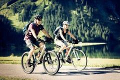 Sêniores do ciclismo pelo lago fotografia de stock