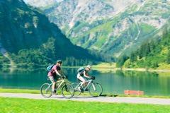 Sêniores do ciclismo pelo lago fotos de stock royalty free