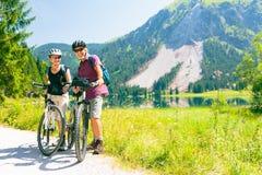 Sêniores do ciclismo pelo lago imagem de stock royalty free