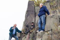 Sêniores e criança que trekking na rocha fotos de stock