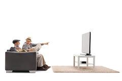 Sêniores em uma televisão de observação do sofá foto de stock royalty free