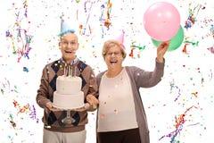 Sêniores extáticos que comemoram um aniversário com um bolo e um balão Fotografia de Stock Royalty Free