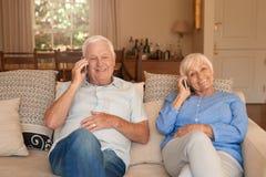 Sêniores felizes que sentam em casa a fala em telefones celulares fotografia de stock