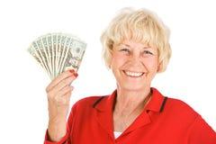 Sêniores: Mulher que sustenta o fã do dinheiro Fotos de Stock