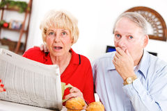 Sêniores: Pares chocados por algo no jornal Foto de Stock