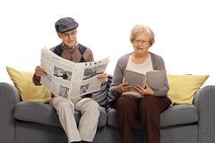 Sêniores que leem um jornal e um livro fotografia de stock royalty free