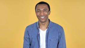 Sì, giovane uomo africano che scuote testa per accettare, fondo giallo video d archivio