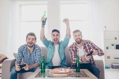 Sì! Gruppo dei vincitori! Gli uomini allegri felici stanno sedendo sul sofà e sulla p immagini stock libere da diritti
