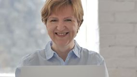 Sí, mujer mayor positiva que acepta oferta sacudiendo la cabeza almacen de video