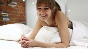 Sí por la mujer joven que miente en la cama, sacudiendo la cabeza para estar de acuerdo metrajes