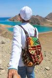 Sígame al mar, mujer con un backbag colorido que dirige al mar con las montañas Fotos de archivo