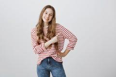 Sígame allí Tiro del estudio del adolescente amistoso confiado con el pelo rubio y la sonrisa positiva en rayado elegante Fotos de archivo