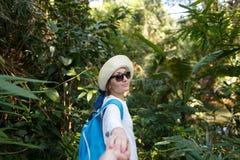 Sígame concepto del recorrido Opinión trasera la mujer joven con la mochila al aire libre que descubre la selva que lleva a cabo  Imagenes de archivo
