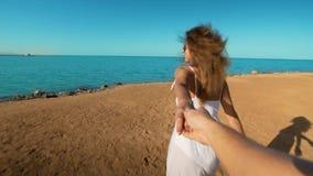 S?game de la mujer joven para tirar de su novio en la orilla de mar La muchacha que lleva a cabo la mano y el funcionamiento masc almacen de metraje de vídeo