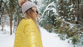 Sígame en el bosque de la nieve, muchacha feliz Mujer joven que lleva a un hombre adelante a la aventura metrajes