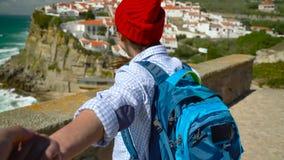 Sígame - la mujer joven feliz en un sombrero rojo y con una mochila detrás de su mano del ` s del individuo que tira en Azenhas e metrajes