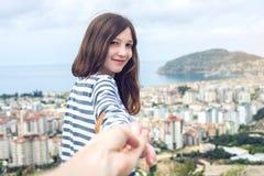 Sígame, muchacha morena atractiva que celebra las ventajas de la mano en la ciudad costera de una altura imagen de archivo