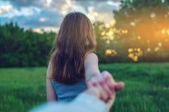 Sígame, muchacha morena atractiva que lleva a cabo la mano de las ventajas en un campo verde limpio con los árboles en la puesta  imagenes de archivo
