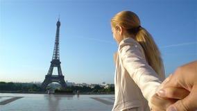 Sígame mujer feliz de París que lleva a su novio a la torre Eiffel almacen de metraje de vídeo