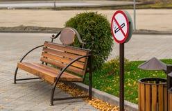 Símbolo, área de fumo, com os bancos no parque sob a construção fotos de stock royalty free