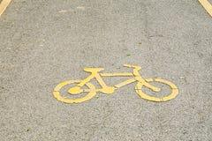 Símbolo amarelo da bicicleta na estrada Trajeto da bicicleta no parque público ou na cidade imagem de stock royalty free