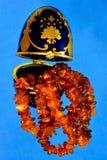 Símbolo ambarino dos grânulos da alegria, divertimento em uma caixa dos ovos da páscoa, em um fundo azul brilhante foto de stock royalty free