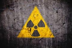 Símbolo amonestador del peligro nuclear atómico radiactivo de la radiación ionizante en fondo oscuro del muro de cemento imágenes de archivo libres de regalías