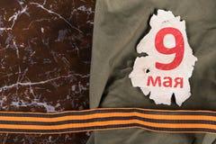Símbolo anaranjado de la cinta de la victoria y de la inscripción el 9 de mayo en el fondo del papel Imagen de archivo