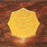 Símbolo antiguo del timón y de la flor del oro en la madera Imagenes de archivo